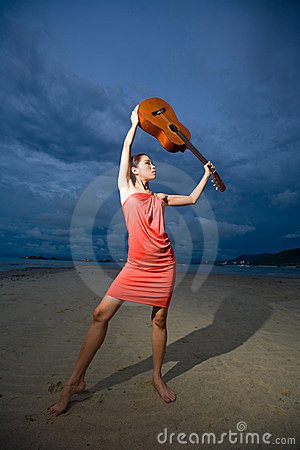 Asian beauty holding a guitar at the beach