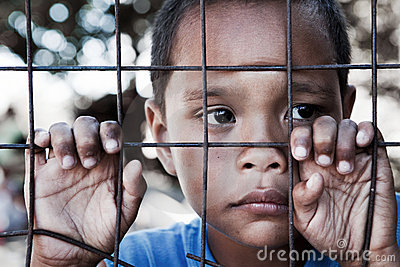 Asian boy against fence with sad expression