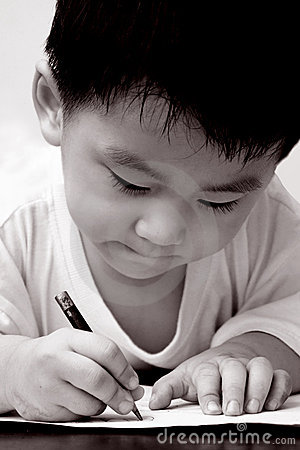 Asian boy drawing on paper