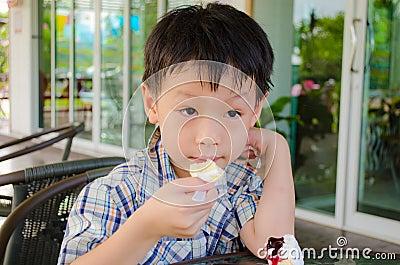 Asian boy eating cake