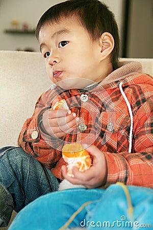 Asian boy eating orange on sofa
