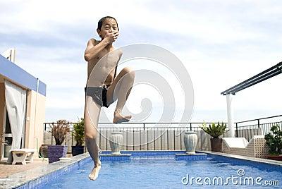 Asian boy jumpin into swimming pool