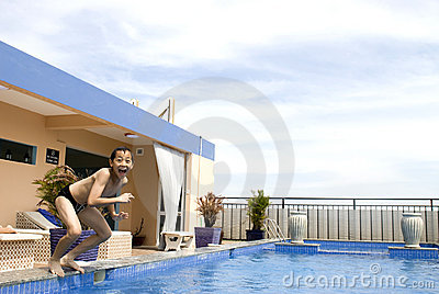 Asian boy jumpin into swimming pool