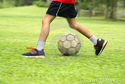 Asian boy kicking soccer ball