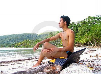 Asian boy with laptop on beach