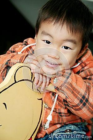 Asian boy lay on hobbyhorse