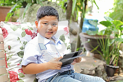 Asian boy playing tablet