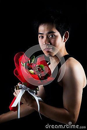 Asian boy with red bouquet in dark background