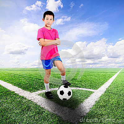 Asian boy with soccer ball at soccer field