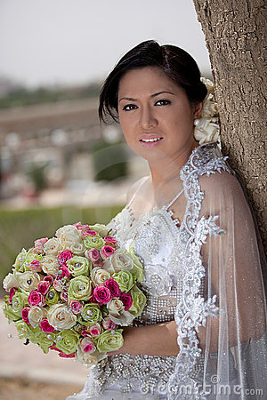 Asian bride outside holding a bouquet