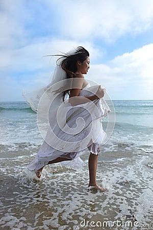 Asian Bride Running Along the Beach