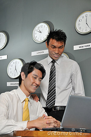 Asian Business executives in room full of clocks
