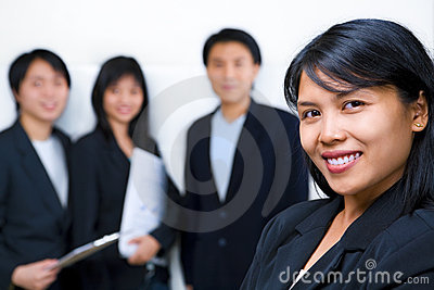 Asian business people with businesswoman in front