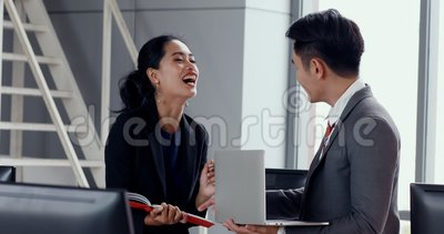Asian business people discuss about report. Asian business people standing and discuss about report, man holding laptop in his hand , woman checking schedule