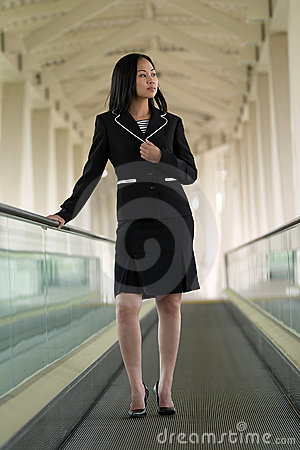 Asian Business Woman on Moving Walkway