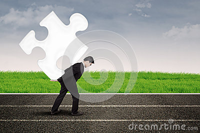 Asian businessman carry puzzle on the road