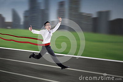 Asian businessman crossing the finish line