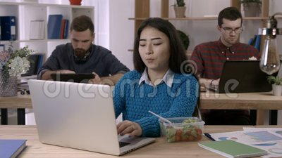 Asian businesswoman eating salad at desk in office stock video footage