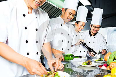 Asian Chef in restaurant kitchen cooking