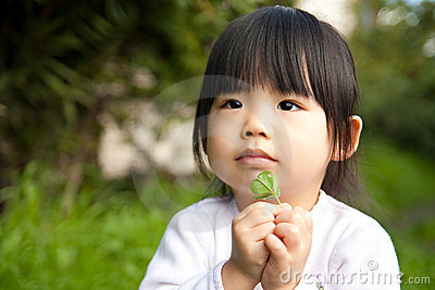Asian child with a leaf on hand