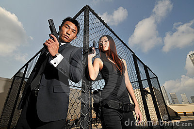 Asian chinese couple carrying guns on rooftop