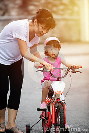 Free Asian Chinese Little Girl Riding Bicycle With Mom Guide Stock Photos - 90084053