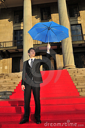 Asian Chinese Man holding umbrella for protection
