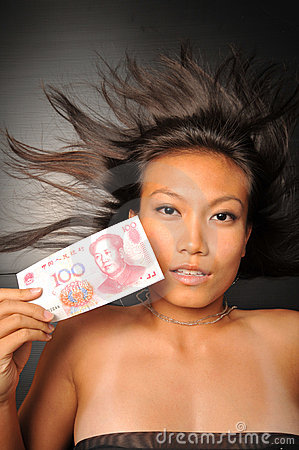 Asian chinese woman holding Yuan close to her face