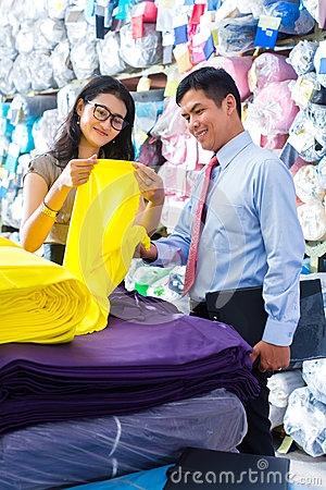 Asian colleagues in a warehouse choosing cloths