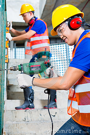 Asian construction workers drilling in building walls