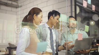 Asian corporate people meeting discussing business in office. A team of young asian corporate people meeting in office discussing business strategies