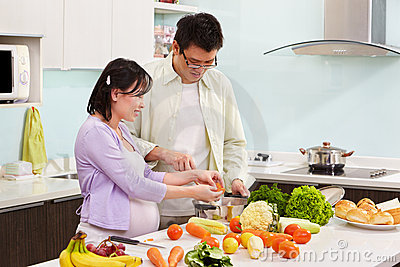 Asian couple busy in kitchen