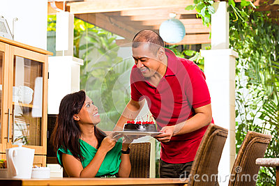 Asian couple having coffee in living room