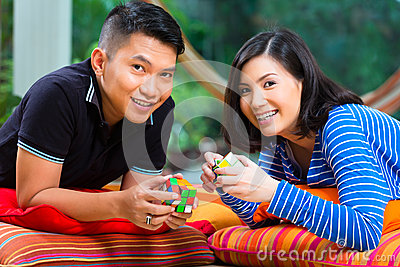 Asian couple at home playing with magic cube Editorial Stock Photo