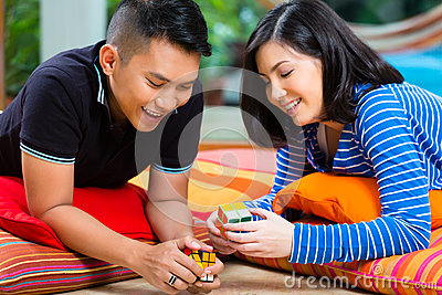 Asian couple at home playing with magic cube Editorial Photo