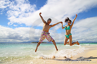 An asian couple jumping on a beach