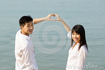 Asian couple making heart symbol