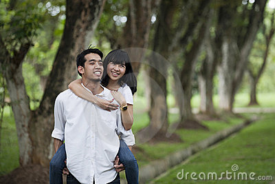 Asian couple piggy back