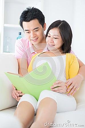 Asian couple reading book