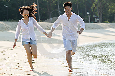 Asian couple running the beach.
