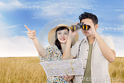 Asian couple using binoculars in field
