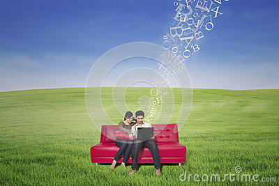 Asian couple using laptop with flying letters outdoor
