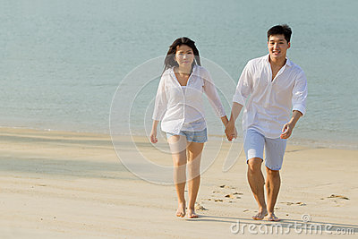 Asian couple walking on the beach.