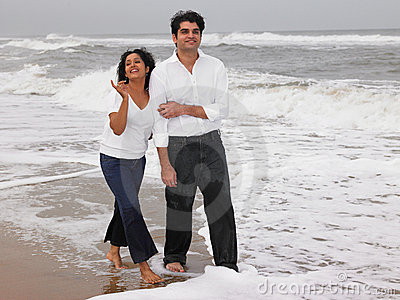 Asian couple walking in the beach