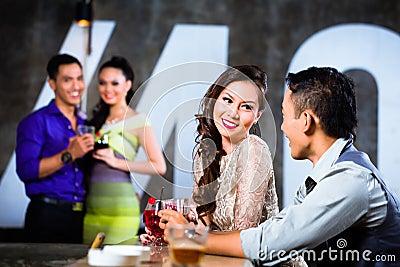 Asian couples flirting and drinking at nightclub bar
