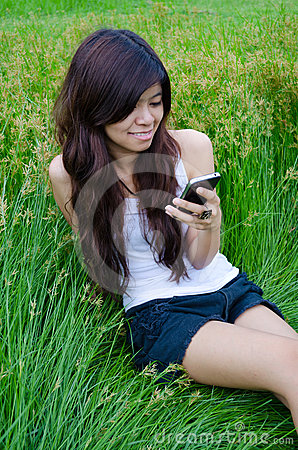 Asian cute girl texting on meadow