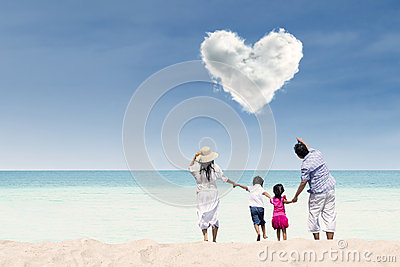 Asian family looking at heart cloud at beach