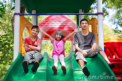 Asian family sitting on playground
