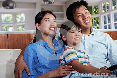 Asian Family Sitting On Sofa Watching TV Together