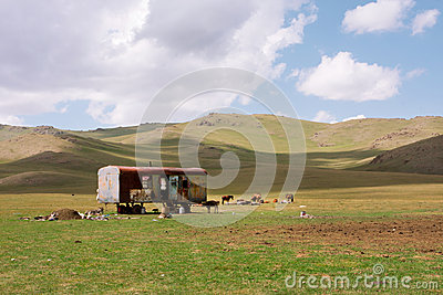 Asian farmers caravan in the meadow of Central Asia with blue sky clouds
